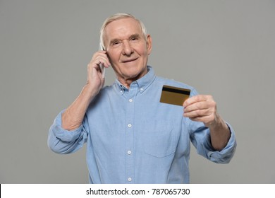 Senior man making a phone call and holding credit card isolated on gray background