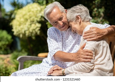 Senior man in medical patient cloth hugging wife outdoor bench. Old woman is consoled by her husband suffering from a terminal illness. Wife visit her husband at the hospital after the operation.