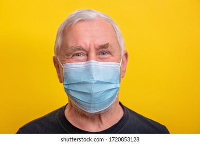Senior man in medicine mask over yellow background with copy space