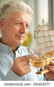 Senior man with miniature ship