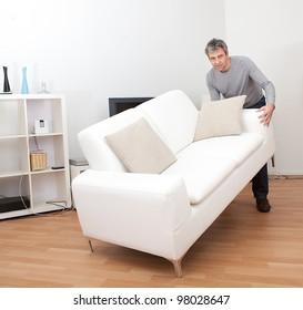 Senior man moving sofa at his home