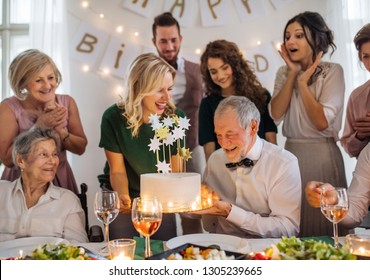 A senior man with multigeneration family celebrating birthday on indoor party.
