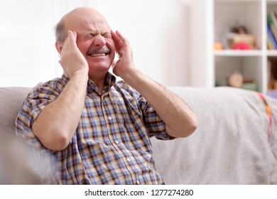 Senior man with mustache having a headache at home
