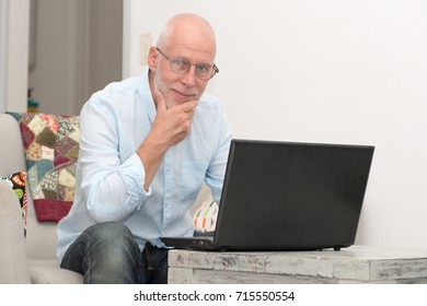 a senior man with notebook sitting in sofa