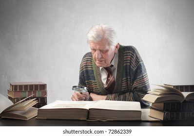 Senior man observing an old book with a magnifying glass