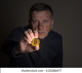 Senior man offering a bitcoin as a bribe or a payment for a ransom or malware