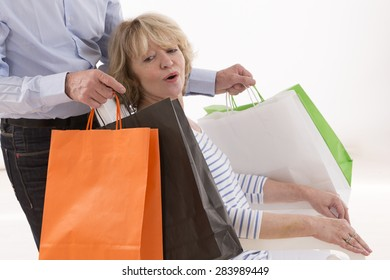 Senior man offering multiple gift bags to woman