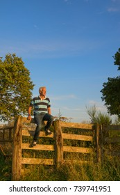 Senior man on agriculture fence in the meadows
