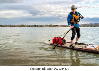 senior man on expedition stand up paddleboard with a large waterprood duffel on deck, a lake in Colorado