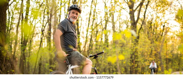 Senior man on his mountain bike outdoors (shallow DOF; color toned image) - panoramic shot