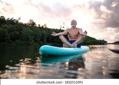 Senior man on paddleboard on lake in summer, doing yoga exercise.