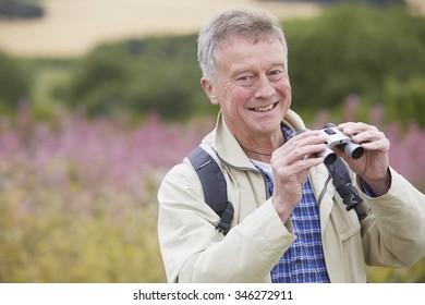 Senior Man On Walk With Binoculars