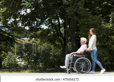 Senior man on a wheelchair going on a walk in the park with a young caregiver