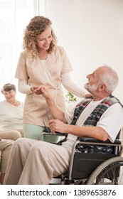 Senior man on wheelchair with helpful nurse holding his hand