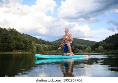 Senior man paddleboarding on lake in summer. Copy space.