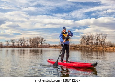 senior man is paddling an inflatable stand up paddleboard on a lake in fall or winter scenery in Colorado