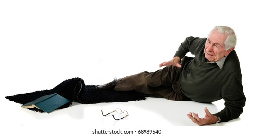 A senior man in pain after slipping on an area rug.  Isolated on white.