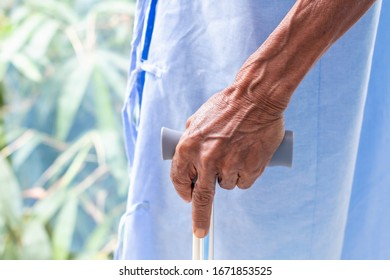 Senior man patient with walking stick in the hospital room.