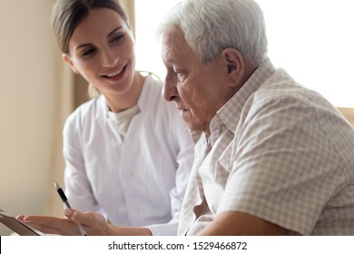 Senior man patient and young woman caregiver medical worker in uniform hold clipboard noting personal information talking listens client telling about health complaints, care support nursing concept