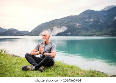 Ein Senior Mann Rentner sitzt auf See in der Natur, Yoga-Übung.