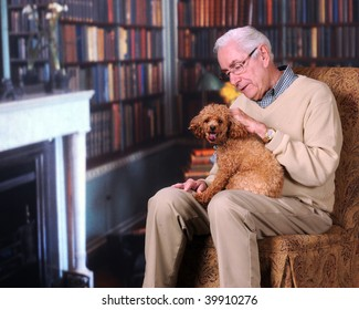 A senior man petting his poodle in a home library/office.