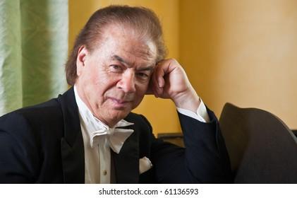 Senior man pianist.  Senior man pianist sitting next to a grand piano.