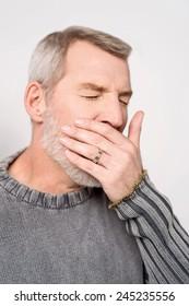 Senior man placing hand on mouth yawning