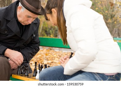 Senior man planning his next chess move staring down at the chess pieces on the board intently as he plays a game with his daughter as they sit together on a wooden park bench