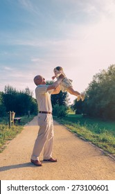 Senior man playing with adorable baby girl over a nature background. Grandparents and grandchild leisure time concept.