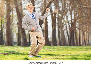 Senior man playing air guitar in the park