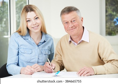 Senior Man Playing Completing Number Puzzle With Teenage Granddaughter