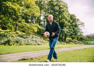 Senior man is playing football at the campsite with his grandchildren who cannot be seen.