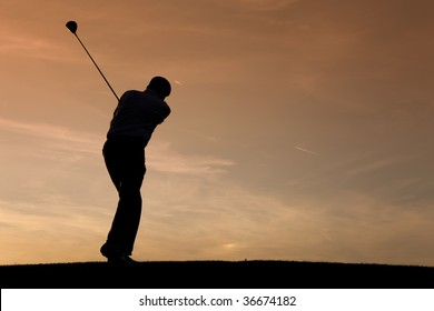 Senior man playing golf - pictured as a silhouette against an evening sky