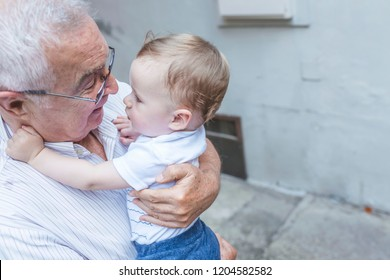 Senior man playing with his grandson at home. Grandfather with baby grandson. Portrait of happy grandson and grandpa, countryside. Grandfather carrying grandson on sunny autumn day