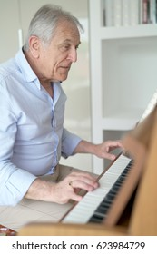 Senior man playing the piano at home