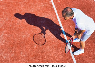 Senior man playing tennis on sunny day
