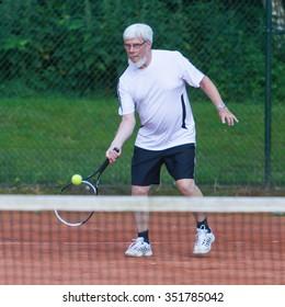 Senior man playing tennis on a gravel court