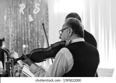 Senior man playing violin at wedding celebration