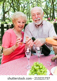 Senior man pops the champagne cork on a picnic with his wife.