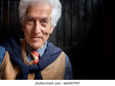Senior man portrait looking at camera. Kind face. Wearing tie and sweater tied over the shoulders. White curly hair and bright intelligent eyes. Close up with copy space on dark background