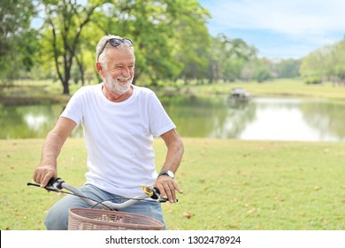 senior man post riding bicycle in the park with clear blue sky (elder healthy concept)