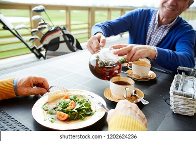 Senior man pouting black tea into cup during lunch with buddy after playing golf