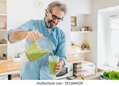 Senior man preparing smoothie in kitchen