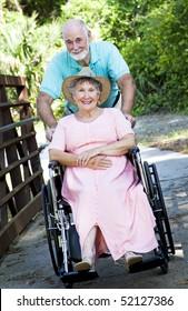 Senior man pushing his disabled wife through the park in a wheelchair.