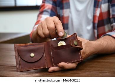 Senior man putting coin into purse at table, closeup