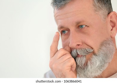 Senior man putting contact lens in his eye on light background