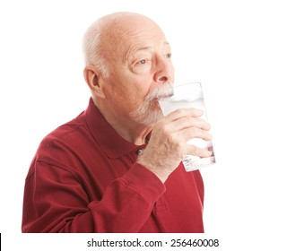 Senior man quenches his thirst with a big glass of filtered ice water.  White Background.