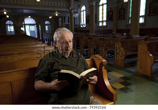 Senior man reading a bible in church