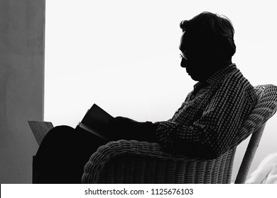 Senior man is reading a book in living room., Black and white