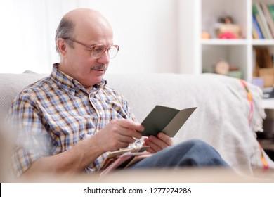 Senior man reading a book on his sofa